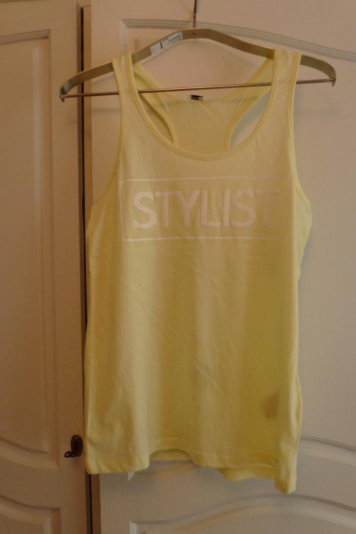 """Un débardeur jaune pastel avec inscrit """"STYLIST"""" : 3.99€"""