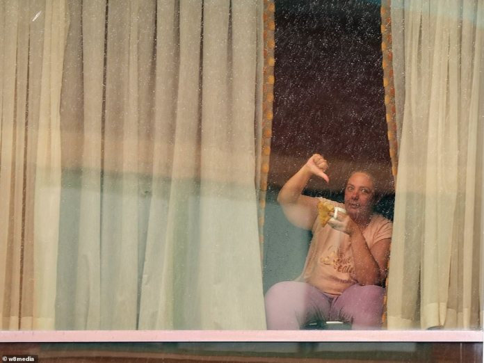 A woman staying in quarantine at the Radisson Blu hotel near Heathrow gives a thumbs down to a photographer this morning