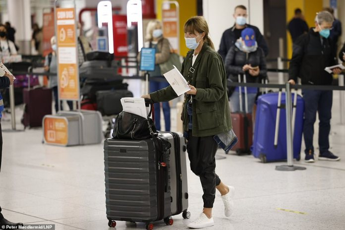 Passengers line up to check-in for early morning flights at Gatwick Airport as global travel restrictions ease today