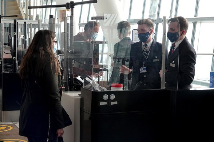 Passengers wearing face masks at Gate A13 boarding their flight to Lisbon, Portugal from London Heathrow today
