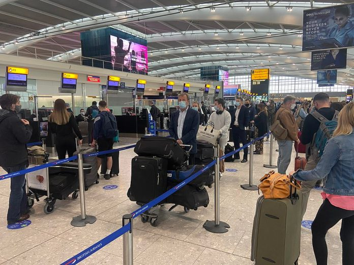Passengers with suitcases seen queueing at check-in at London Heathrow as global travel restrictions are eased