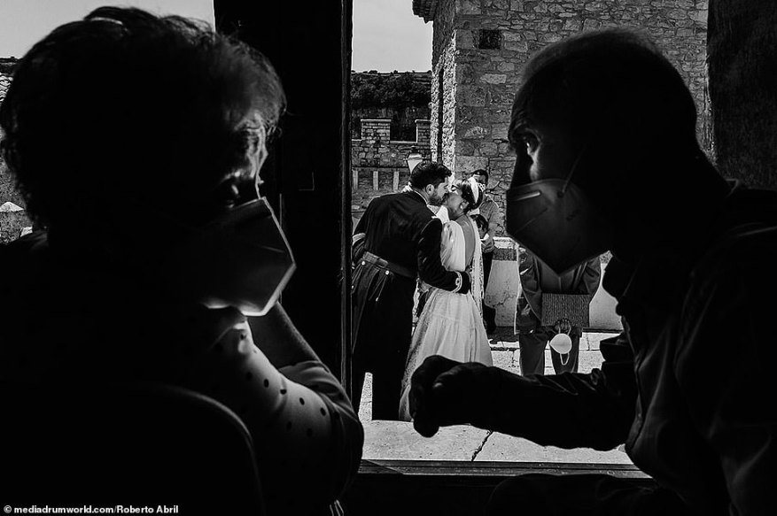 Reality: Only a handful of the images show a glimpse at how wedding celebrations have changed amid the COVID-19 pandemic, withRoberto Abril capturing an elderly couple wearing masks while gazing at one another - as a bride and groom celebrated their nuptials in the background