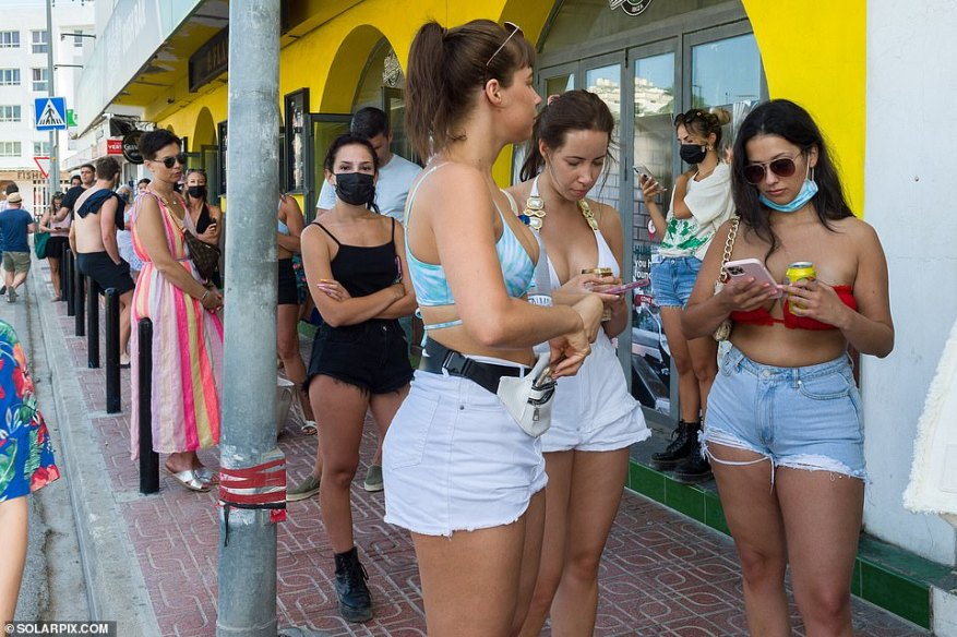 Holidaymakers can be seen queueing outside a clinic in San Antonio to get PCR tests ahead of their flights back to the UK
