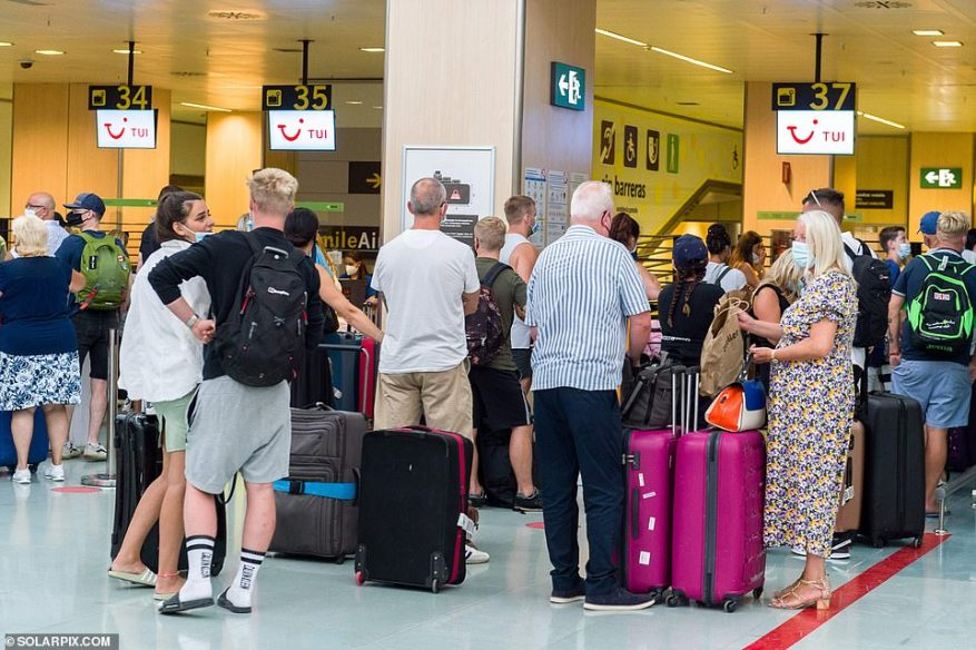 Passengers can be seen queueing at baggage drop-off inside Ibiza Airport ahead of their flights back to the UK