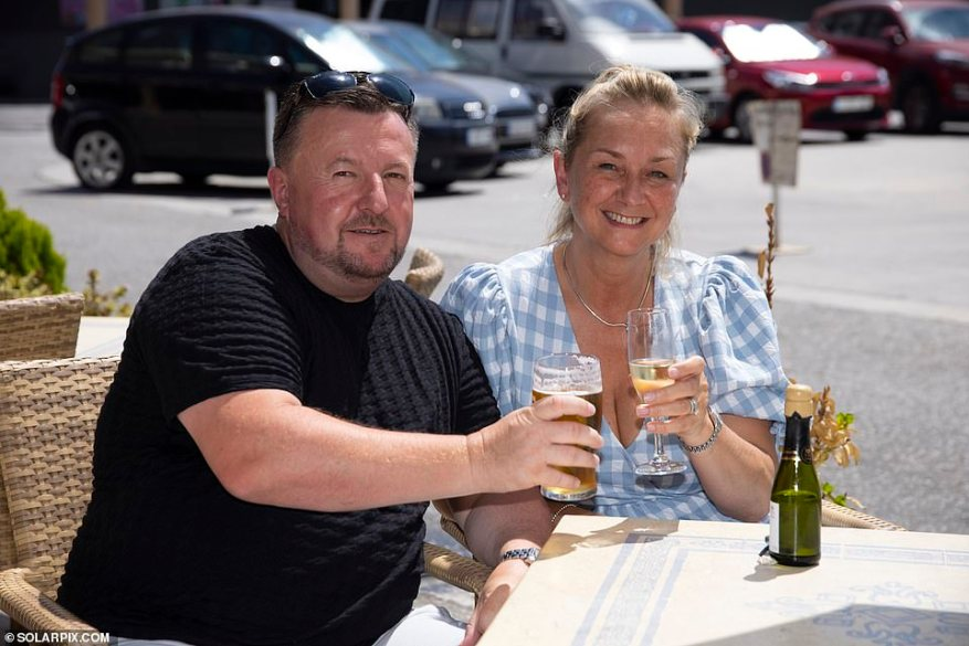 Tony Miller, enjoying his first pint less than an hour after jetting to Malaga with wife Susie, said: 'Luckily we're flying back before August 5 and I buy and sell cars online so I can work off my phone'