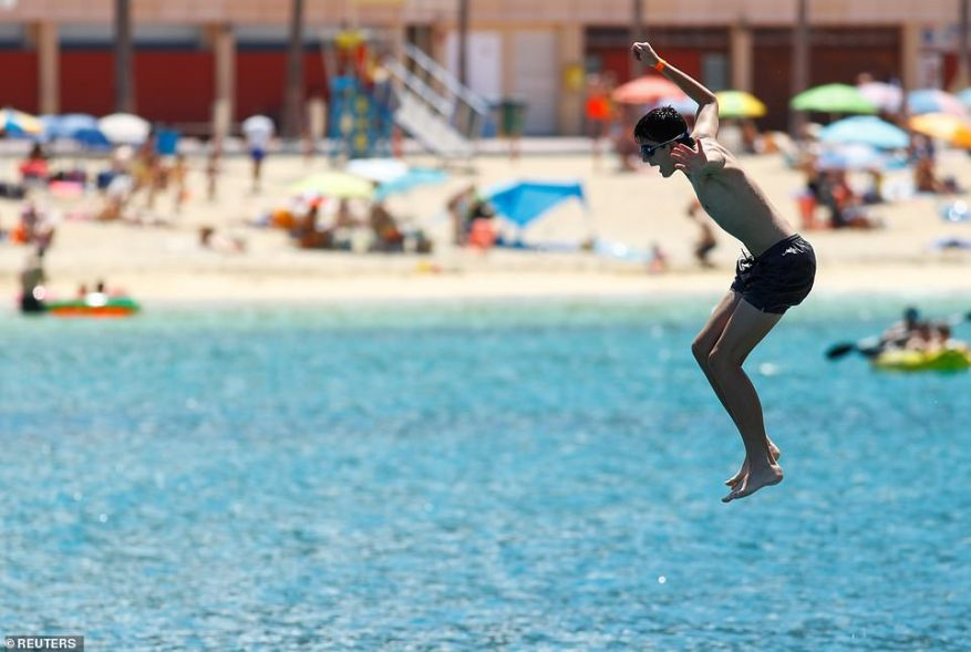 A tourist jumps into the sea on the Amadores beach, amid the outbreak of the coronavirus disease (COVID-19) in the south of the island of Gran Canaria, Spain