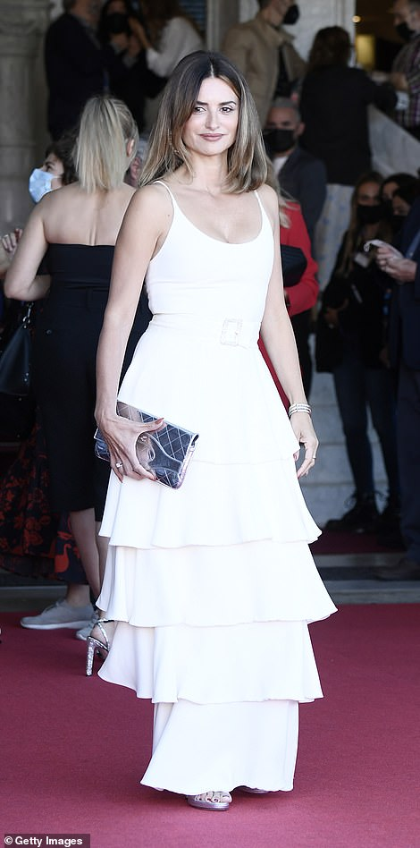 Finishing touches: Penelope accessorised her red carpet look with a metallic purse clutch and heels, while sporting a chunky silver bangle on one wrist