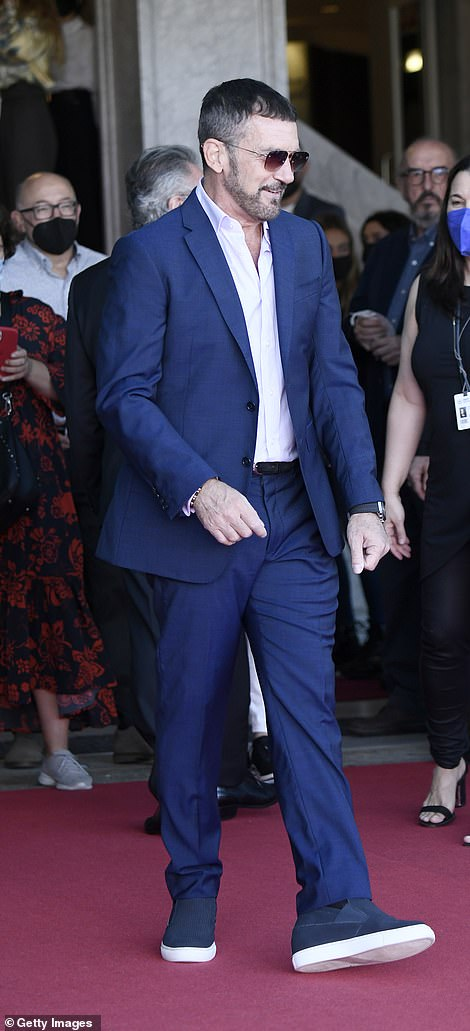 Dressed down: He kept it casual by sporting a pair of plimsoles on his feet