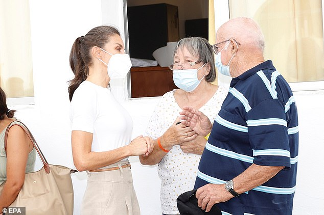To the barracks she wore a simple white t-shirt paired with camel trousers and a brown belt, with her brown tresses tied back in a low ponytail. She is pictured speaking with a couple who were evacuated from their home
