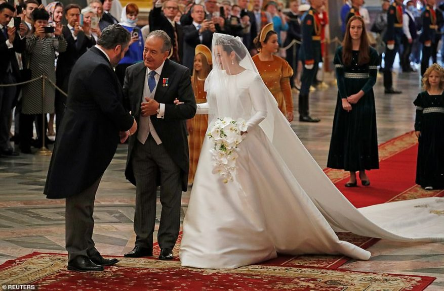 The bride donned a stunning white satin gown which featured a high neck, long sleeves and a billowing skirt, as well as a glittering diamond tiara