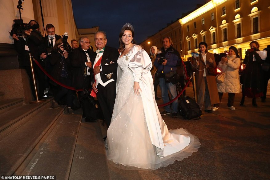 Pictured: Rebecca poses for another photo with her diplomat father on the steps of their reception.