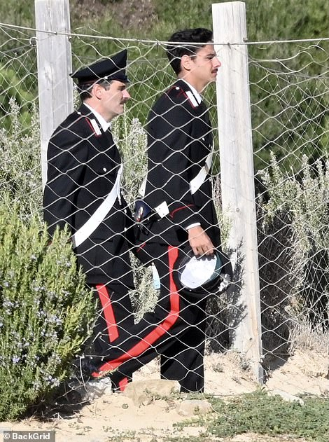Formal: The pair sported black blazers with matching trousers with red stripes