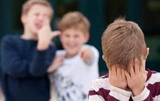 An upset elementary school boy hides his face while being bullied by two other boys as an example of a negative learning environment. Shot in front of their elementary school.