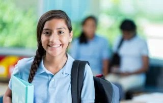 Confident international student before class. She is standing in her classroom. He has a braid and is wearing a backpack and a school uniform. Students are in the background talking.