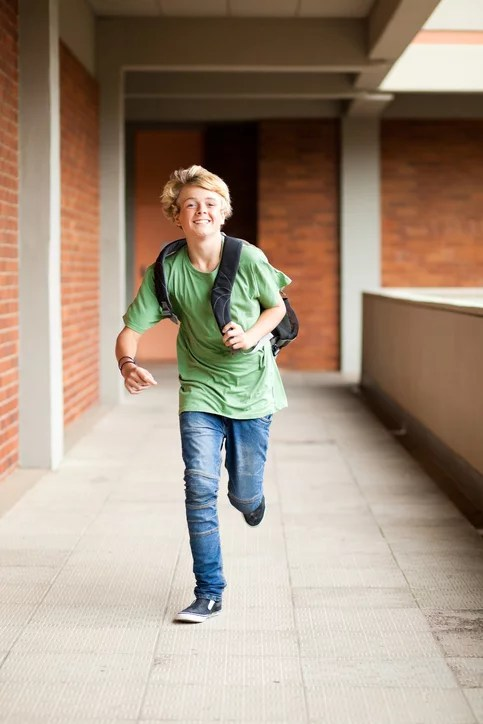 male middle school student running running late for school