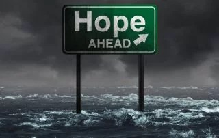 Hope ahead inspirational and motivational life concept as a highway sign drowning in deep flood waters after a hurricane storm as a message of spiritual faith or the promise of recovery and patriotic unity with 3D illustration elements.