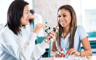 Young Asian female teacher helps teenage private high school student study molecular structure from a customized curriculum. The teacher is holding a plastic educational model. The teenage girl is interested as her teacher talks.