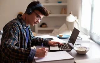 Teenage boy wearing headphones working at desk to finish the semester strong