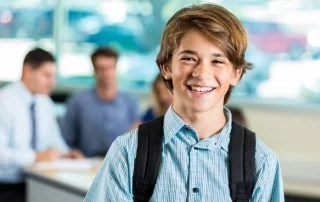 Teenage boy is wearing a backpack and standing in classroom in secondary school