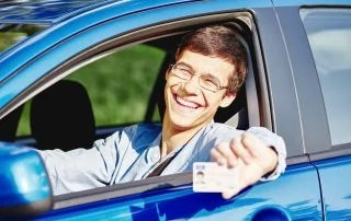Teenager wearing glasses and jean shirt sitting behind wheel and holding out his driver's license through car window