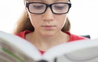 young female 2e student with learning disabilities reading a book in closeup on a white background