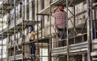 Back view of female and male worker on scaffolding.