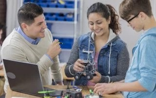 Diverse male and female high school students build a robot in technology class. A male teacher is helping them. Robot parts and a laptop are on the table.