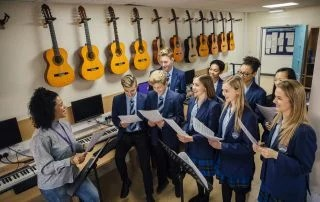 Class of teens are in their music lesson at private schools. There is a female teacher and the class are practicing choir with her.