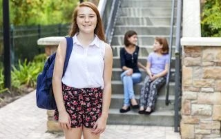 Smiling teenager with a backpack looking into the camera at school