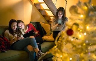 Girl friends sharing on social network together during winter break