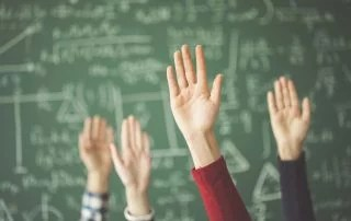 Students raised up hands green chalk board in classroom. Questions in Class