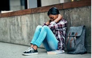 Student anxiety concept, teen girl hunched over against a wall outside