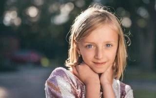 young blonde teenage girl posing outside