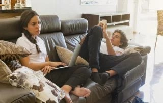 Two teenagers sitting on the couch, texting message and accessing internet with laptop. Summer learning loss concept