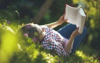 Teen outside in the summer reading in the garden