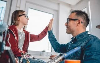 Father and daughter talking about alternative school while working on electronics components at home office and cheering after successful testing