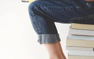 Gifted and talented student sits on a stack of books reading