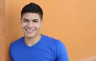 Smiling hispanic teen boy. International students and private education concept.