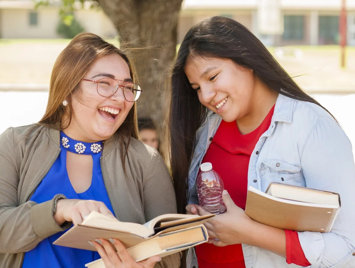 Multi-ethnic group of high school girls talking together outdoors. The Hispanic and Native American group of girls are holding textbooks and backpacks. The school building is in the background. Another girl is sitting by tree. International students