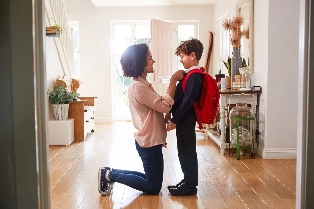 Mother At Home Getting Son Wearing Uniform Ready For First Day Of School. Transitioning to middle school concept
