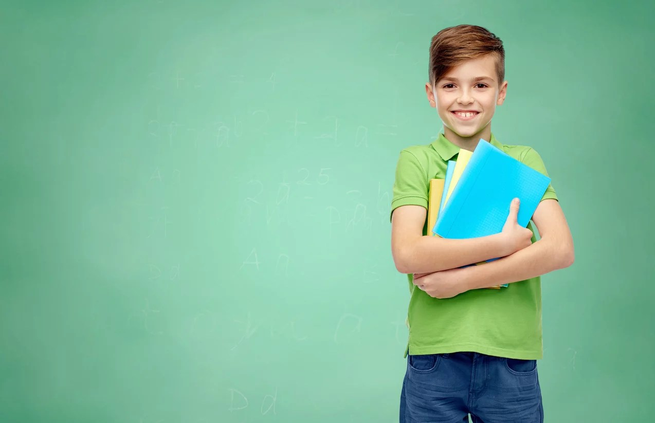 Gifted and talented boy student with folders and notebooks over green school chalk board background