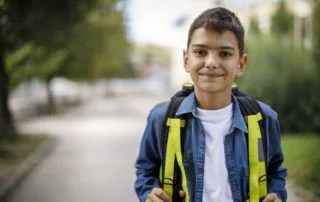 Smiling teenage boy with school bag in front of school. Difficulties international students face concept