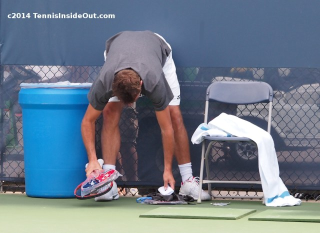 Stan Wawrinka bent over reaching down for racquets wristbands gear racket towel practice Federer Cincy