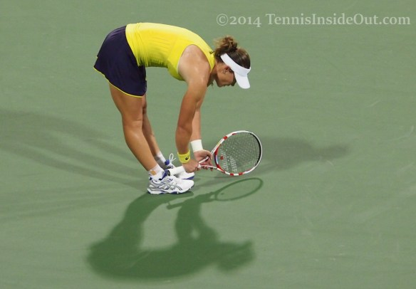 Cincinnati tennis Sam Stosur bent over stretching racquet yellow purple kit