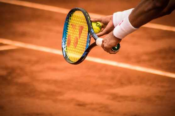 close up photo of person holding tennis racket and ball