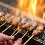火であぶられた、焼き鳥と料理人の手