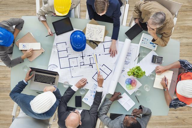 新しいプロジェクトについて図面を見て議論する建築家