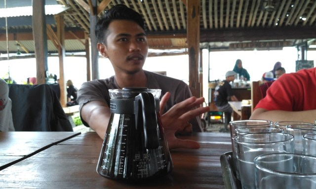 Foto: Mas Danu selaku barista kedai sabin sedang menjelaskan seduhan kopi Robusta Leksana yang disajikannya