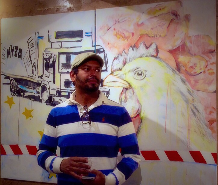 "Omar Castañeda With his painting ""Food Inc. Refugees"""