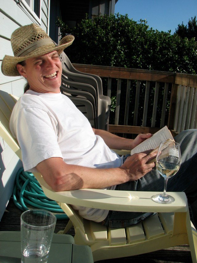 Eric, sporting his vacation hat, reads me ridiculous names from one of the books we brought to the beach.